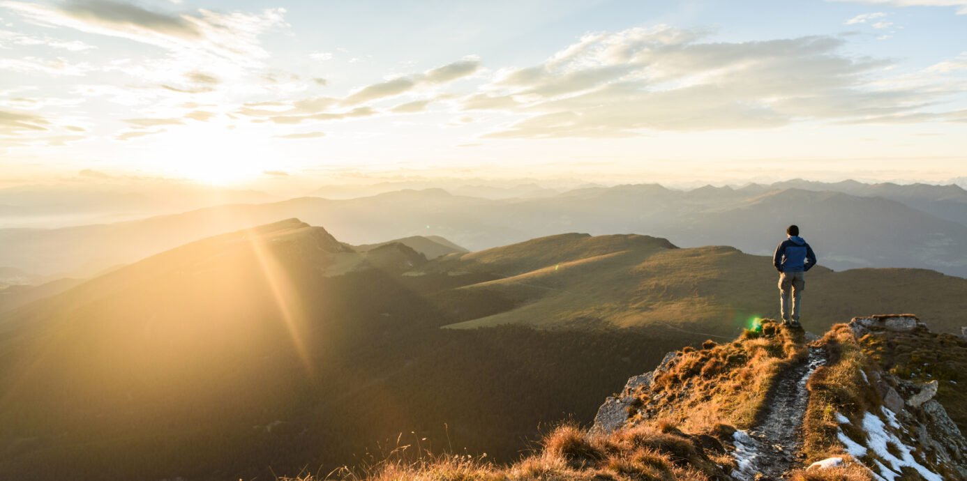 Man Standing on Mountain Looking at Sunset