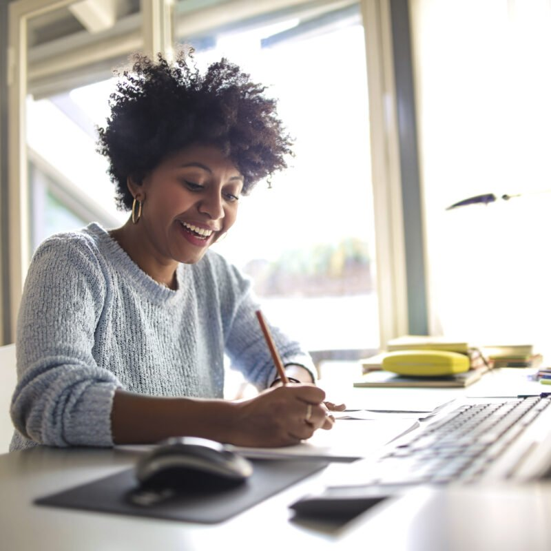 woman at office smiling while working hard using PAIRIN for development