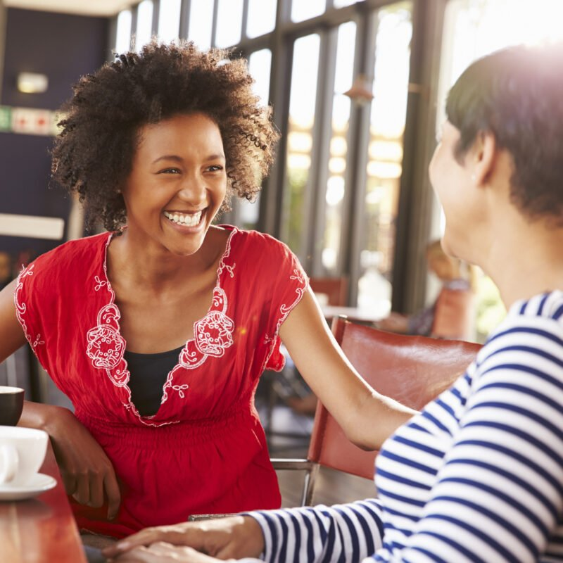 two women smiling and laughing at a sunny coffee shop
