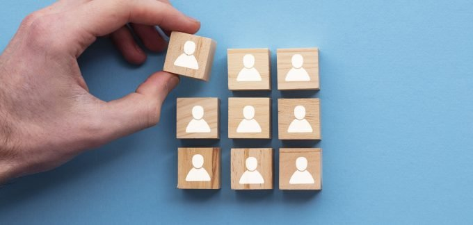 Person stacking blocks with people icons