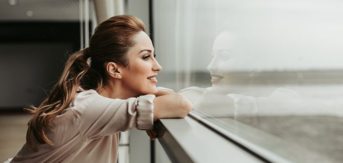 Woman looking out a window smiling