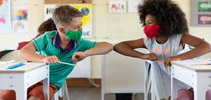 two kids in a classroom with masks bumping elbows